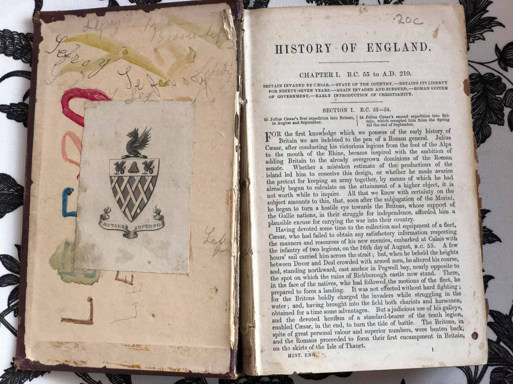 End page and first page of old book published circa 1841 'School History of England'. Printed by John W Parker and Son (London). Spine is broken and pages missing. Lefroy is written multiple times over inside cover in pencil and coloured paint. A bookplate with a crest has been stuck over the writing - reads MUTARE SPERNO
